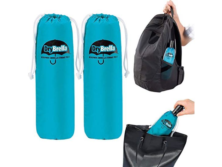 Two Drybrella bags next to a backpack and a purse with umbrellas wrapped in Drybrellas inside