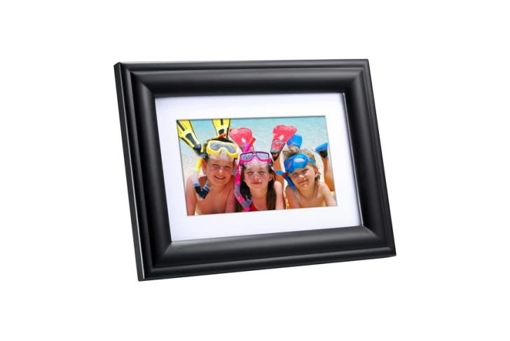 A photo frame with a photo of three children at the beach inside