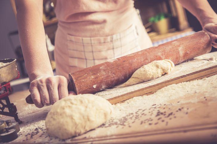 A baker rolls bread dough