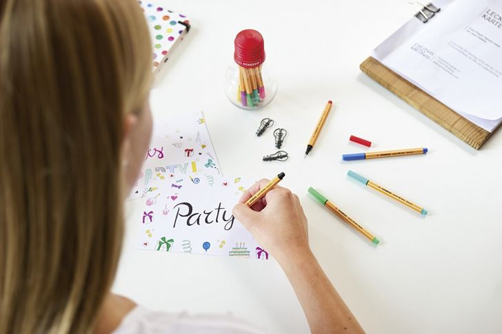 A woman writes 'Party' on with Stabilo Fineliner pens