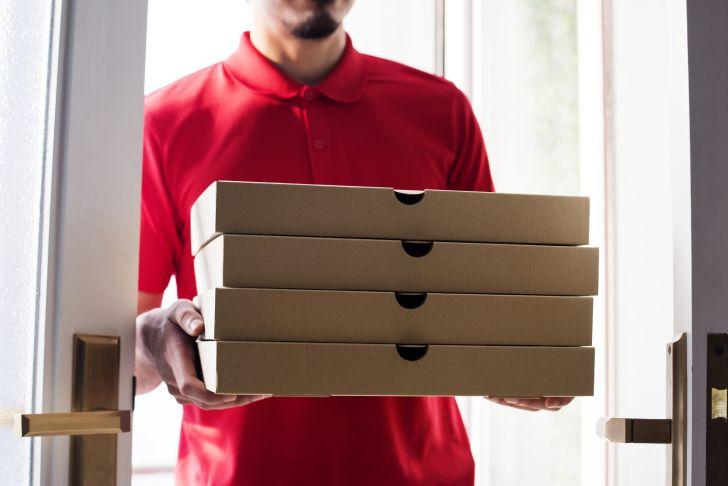 Man delivers several pizzas to a customer