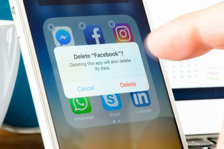 A finger deleting the Facebook app from a smartphone
