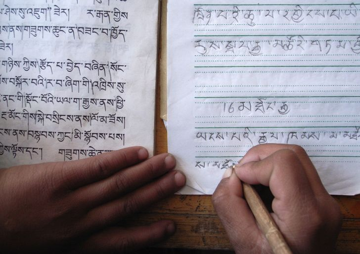 A student writes the Tibetan script