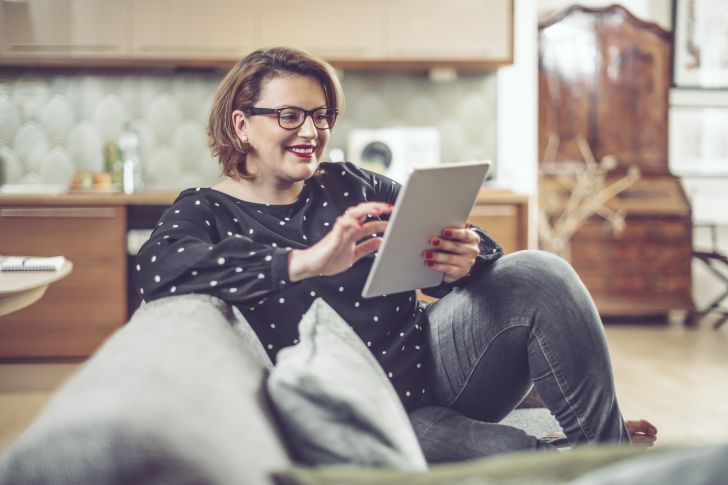 A smiling woman seated on a couch using a tablet