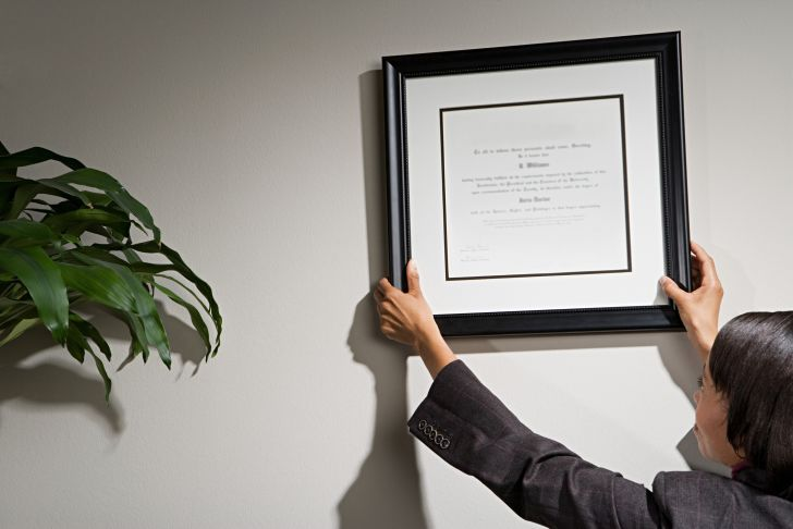A businesswoman hanging a framed certificate