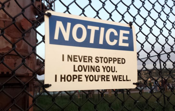 Public warning sign art on chain link fence.