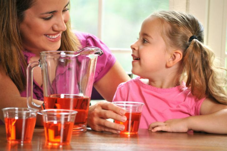 A mother serves Kool-Aid to her daughter