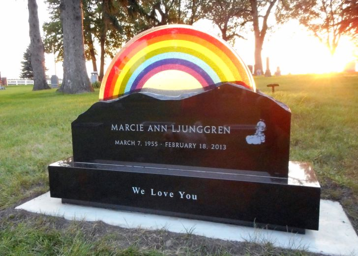 A headstone designed with a rainbow on top of it that reads 'Marcie Ann Ljunggren'