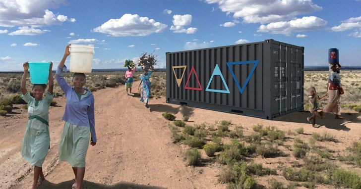 Women carrying water buckets on their heads walk past a shipping container.