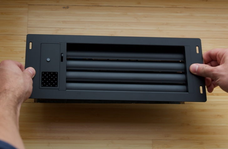 A black vent sits on the floor before installation.