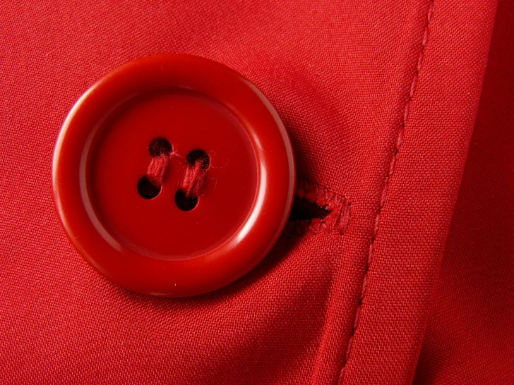 A red button appears on red fabric