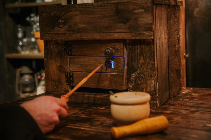 A person taps a wand on a wooden box in a mixology class.