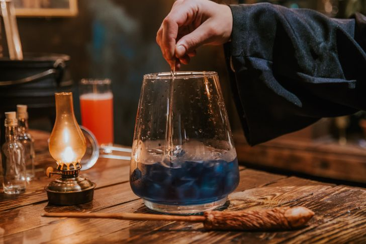 A person in a robe stirs a blue cocktail.