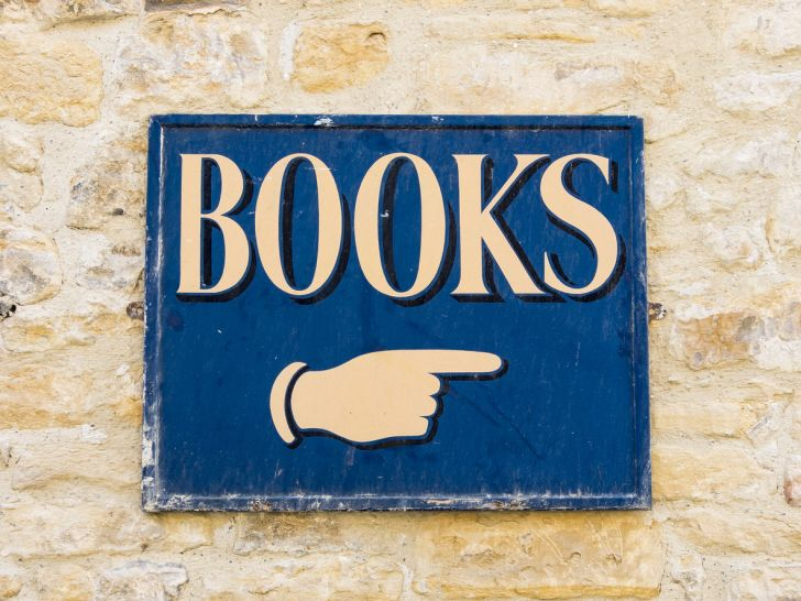"""A blue sign with white letters spelling out the word """"books"""" and a hand pointing"""