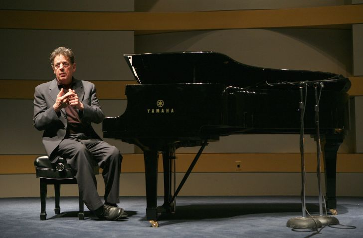 Composer Philip Glass sitting at a grand piano.
