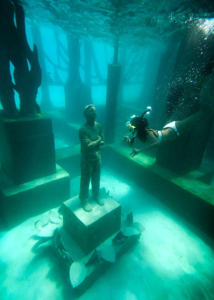 A snorkeler looks at a submerged sculpture