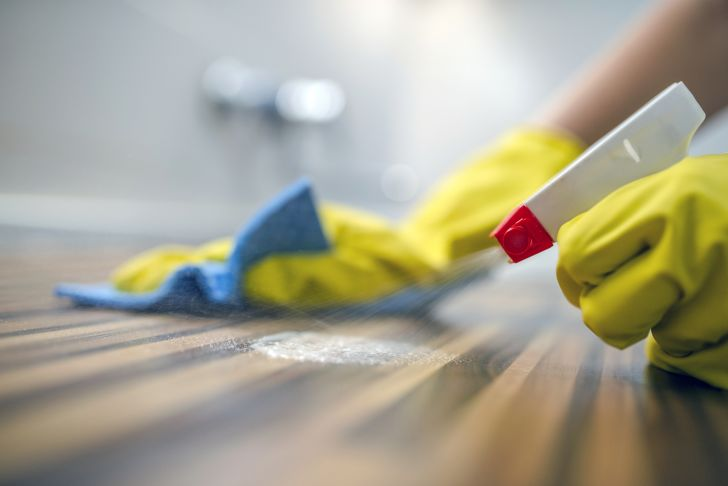A person cleaning a table top with spray and a cloth.