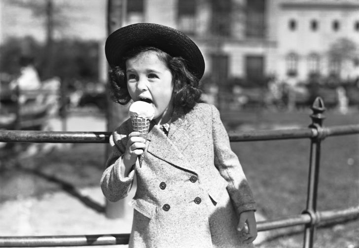 black and white photo of a young well-dressed girl eating an ice cream cone