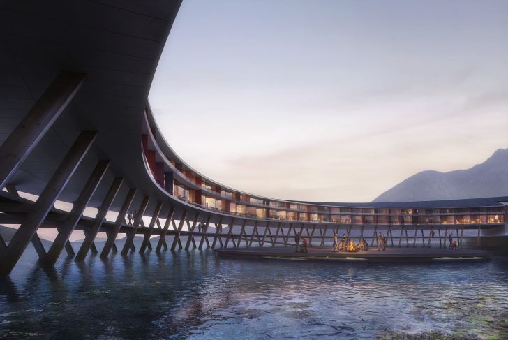 A hotel stretches out above the water of a fjord.