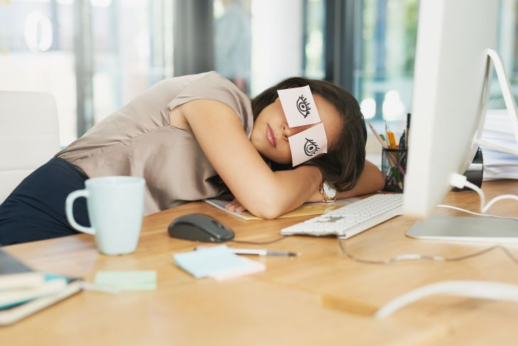 A woman naps at her desk