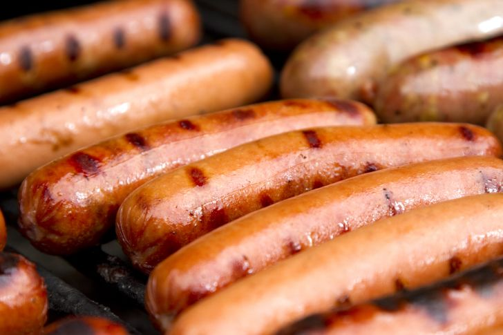 Image of hot dogs being cooked on a grill