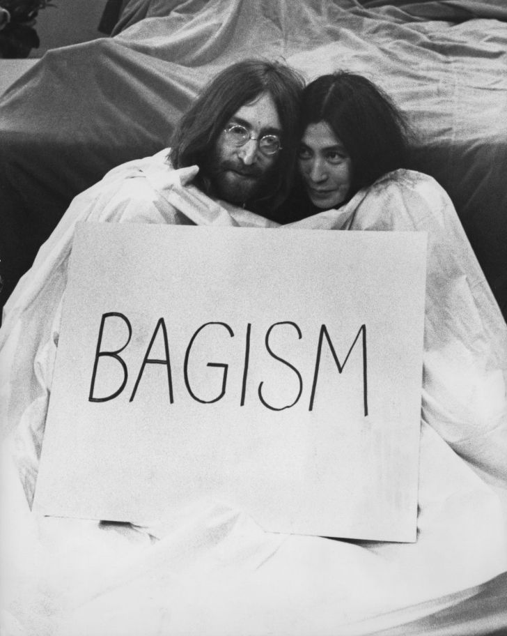 """John Lennon and Yoko Ono with a sign reading """"bagism"""""""
