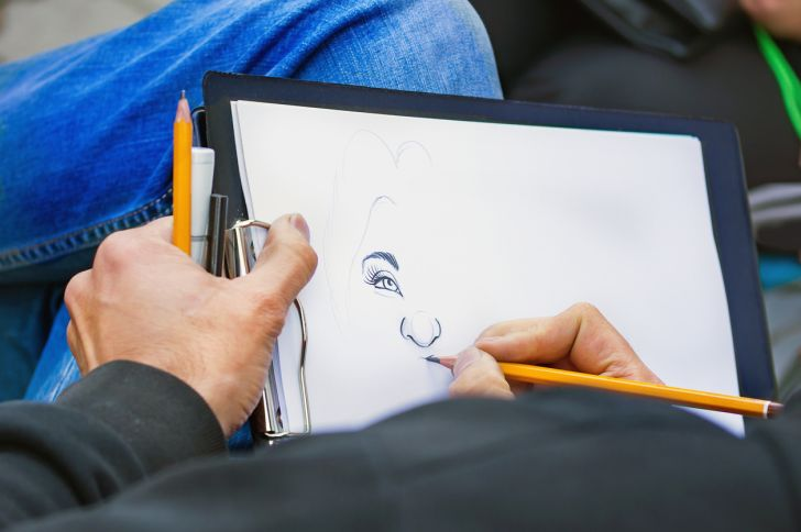 Man's hands with pencils drawing a woman's portrait