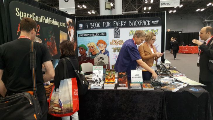 Visitors stop by a Space Goat Productions convention table