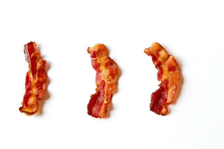 Three strips of bacon on a white background