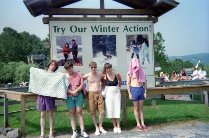 A group of Action Park visitors poses for a photo with the Cannonball Loop behind them
