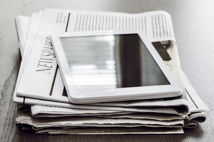 stack of newspapers and tablet
