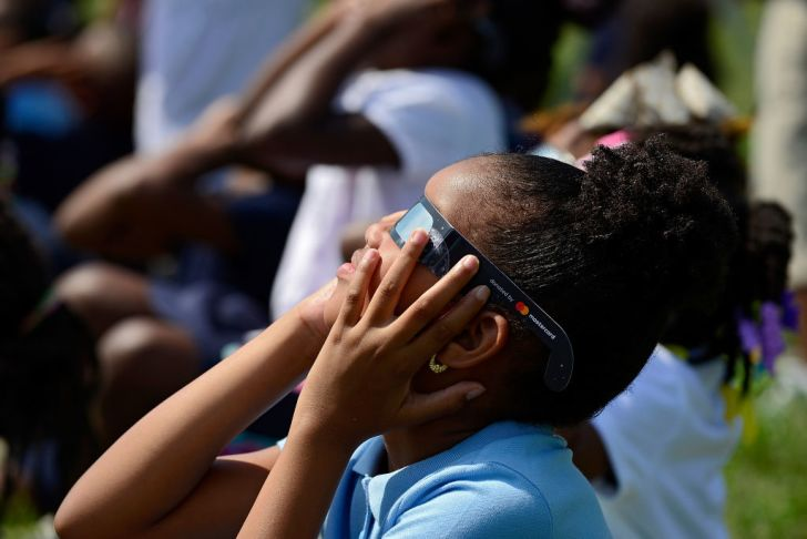 girl in eclipse glasses looks up at the sun