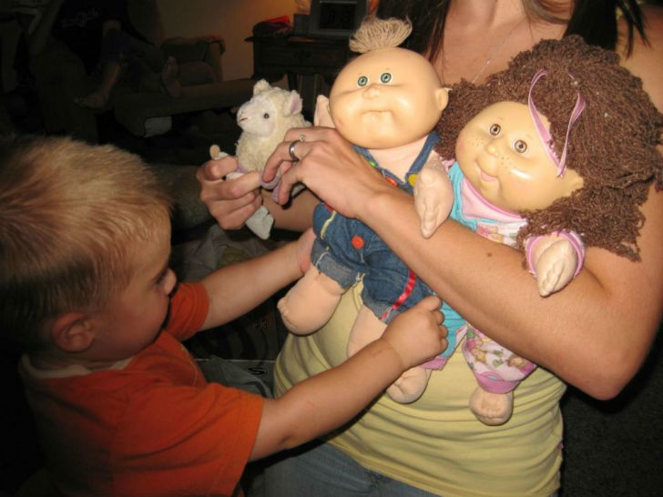 A child examines two Cabbage Patch Kid toys