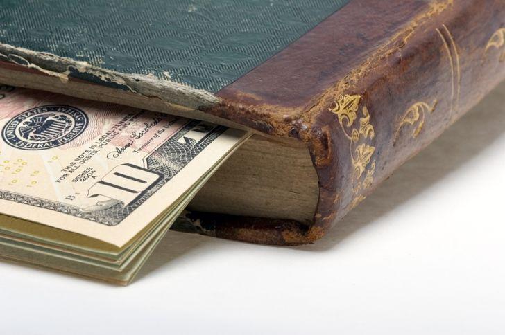 A stack of bills inside an older book