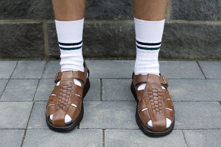 Photo of man in white socks and sandals.