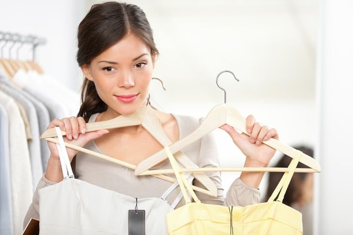 A woman contemplating two different dresses on wooden hangers