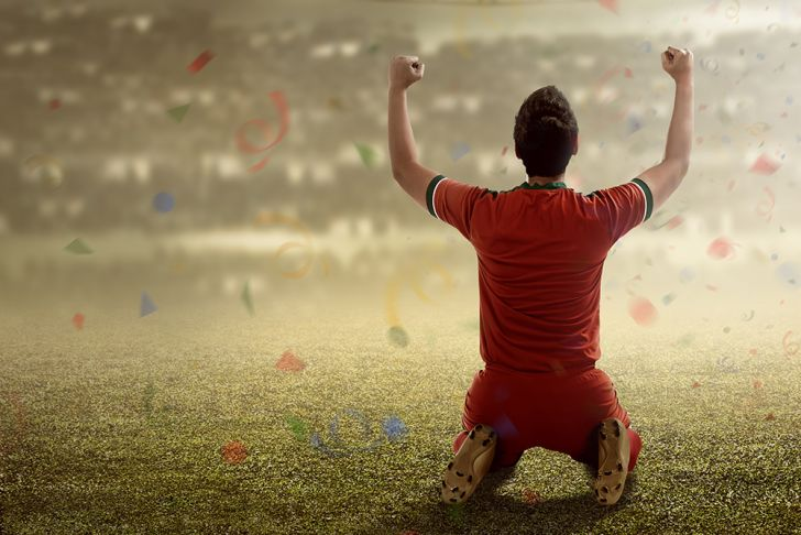 A man sitting on football field, arms raised in victory, as confetti flutters down