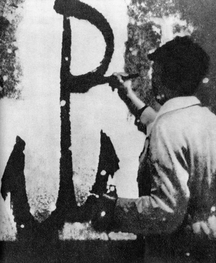 The symbol of the Polish resistance being painted on a wall in German-occupied Poland.
