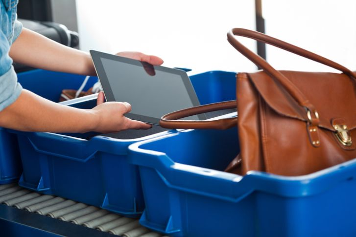 woman putting an ipad into a bin at airport security