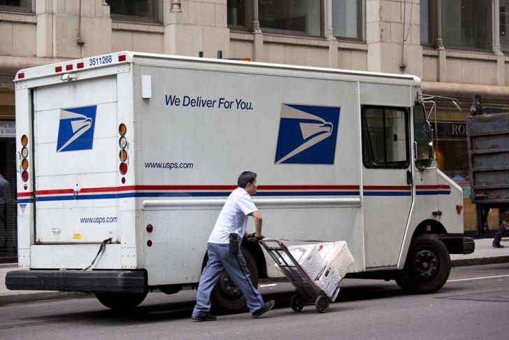 66d45da501 postal worker walking next to a mail truck