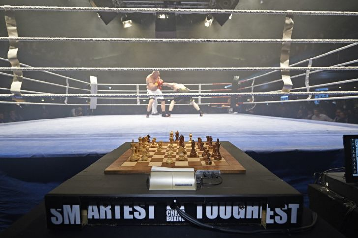 A chess board awaits two boxers between rounds