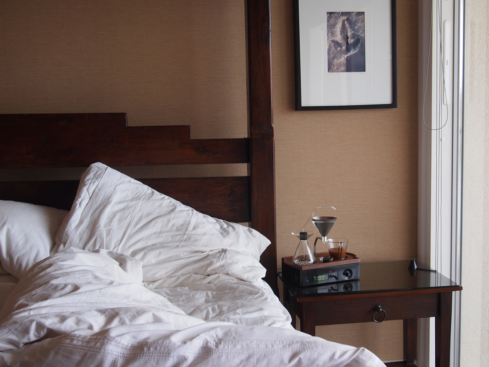A coffee alarm clock next to a bed