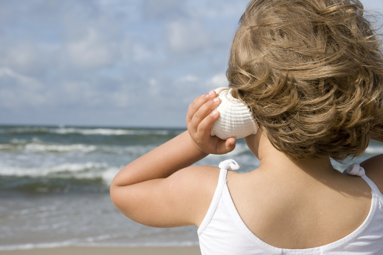 A child holds a seashell up to her ear