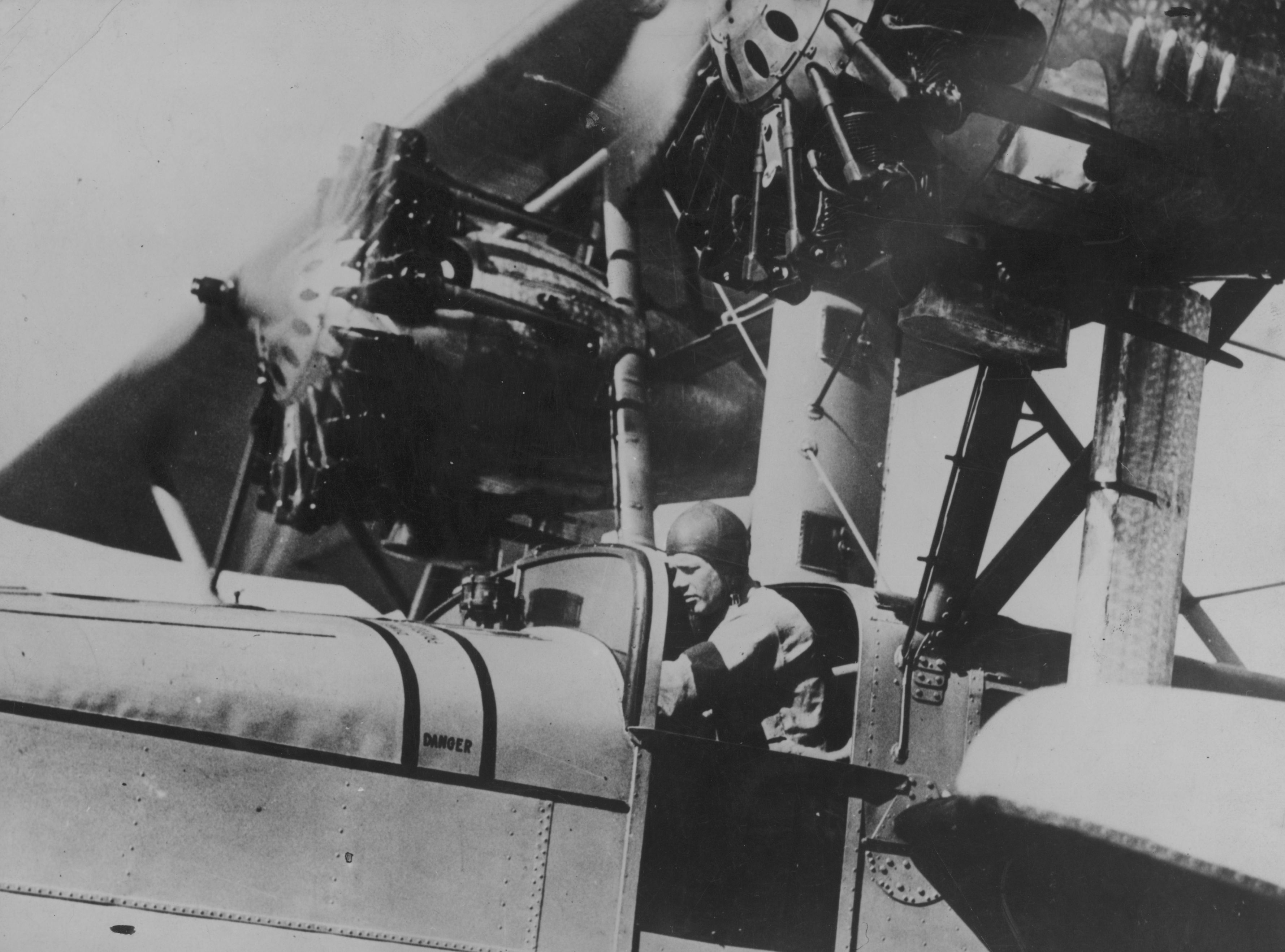Black and white photo of pilot Charles Lindbergh in the cockpit of a postal plane.